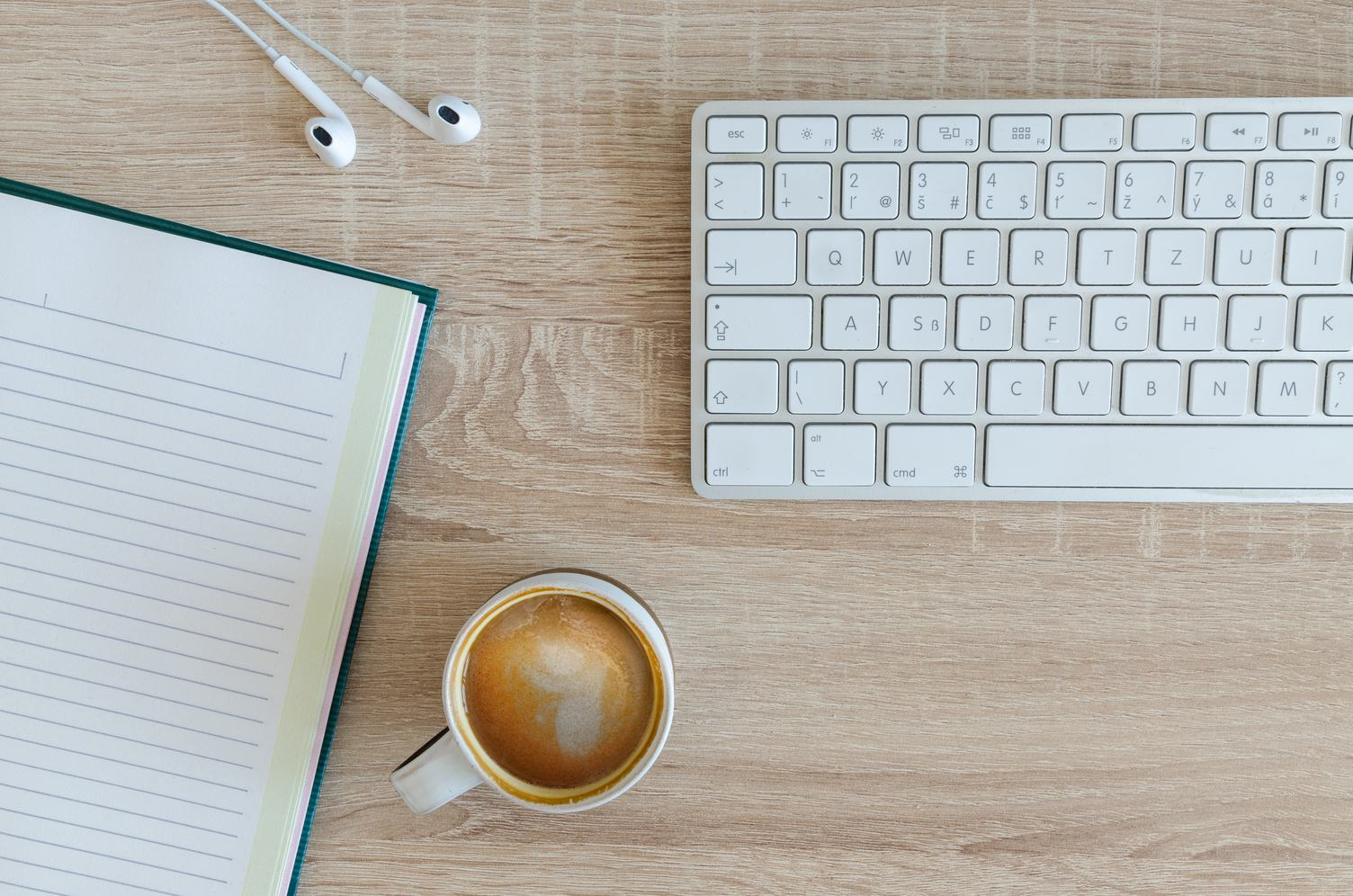 Flat Lay Photo of Wooden Desk with Keyboard, Notebook, Earphones and Coffee