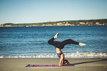 Young Woman Does Yoga on the Beach