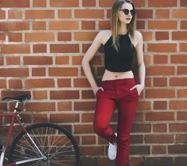 Young Woman with Her Bike Leaning against Red Brick Wall