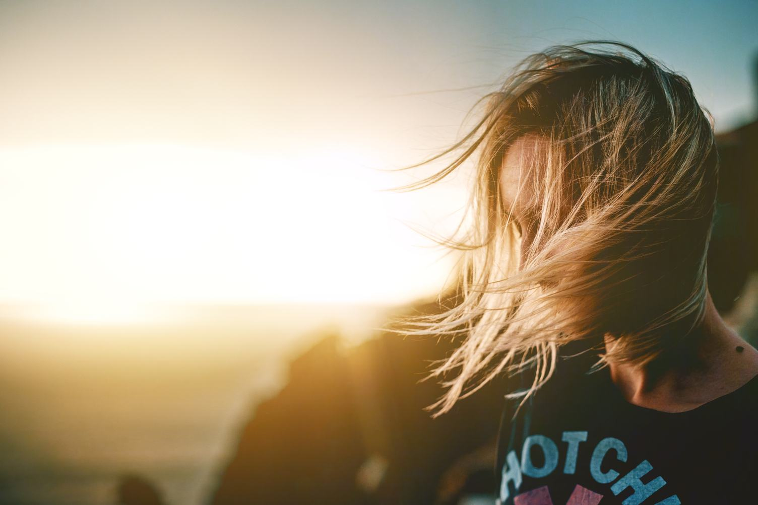 Face of Young Woman Hidden in Wind-Blown Hair
