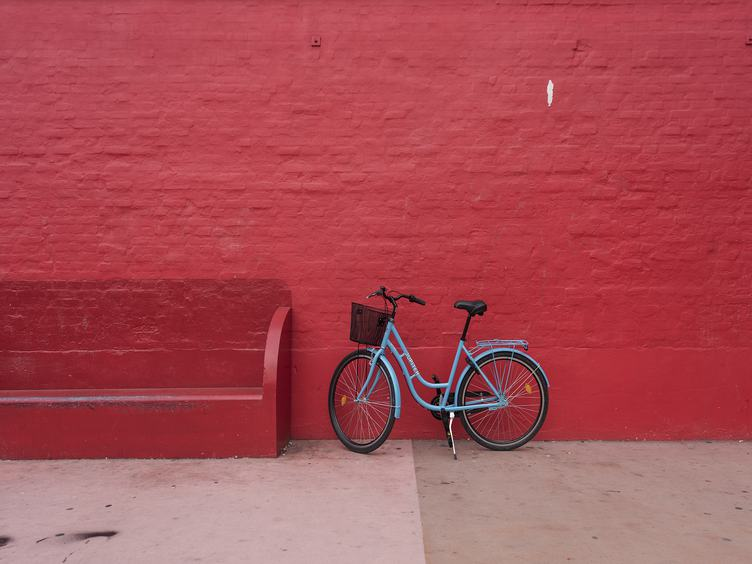 Blue Bicycle against Red Brick Wall