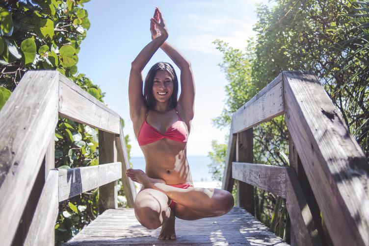 Happy Young Woman in Pink Bikini Practicing Yoga near the Beach