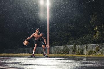 Athlete Male Playing Basketball at Rainy Night Outdoors