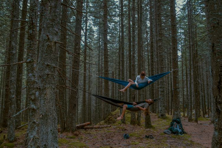 Couple Who Loves to Travel Relaxing in Two Hammocks in the Forest