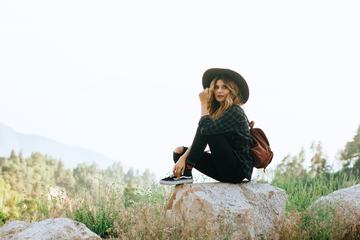 Woman with Backpack Sitting on the Rock