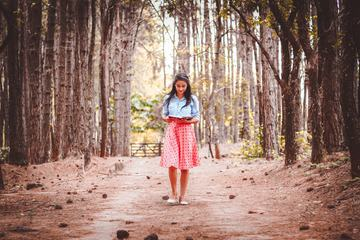 Cute Brunette Walking and Reading Book in the Forest
