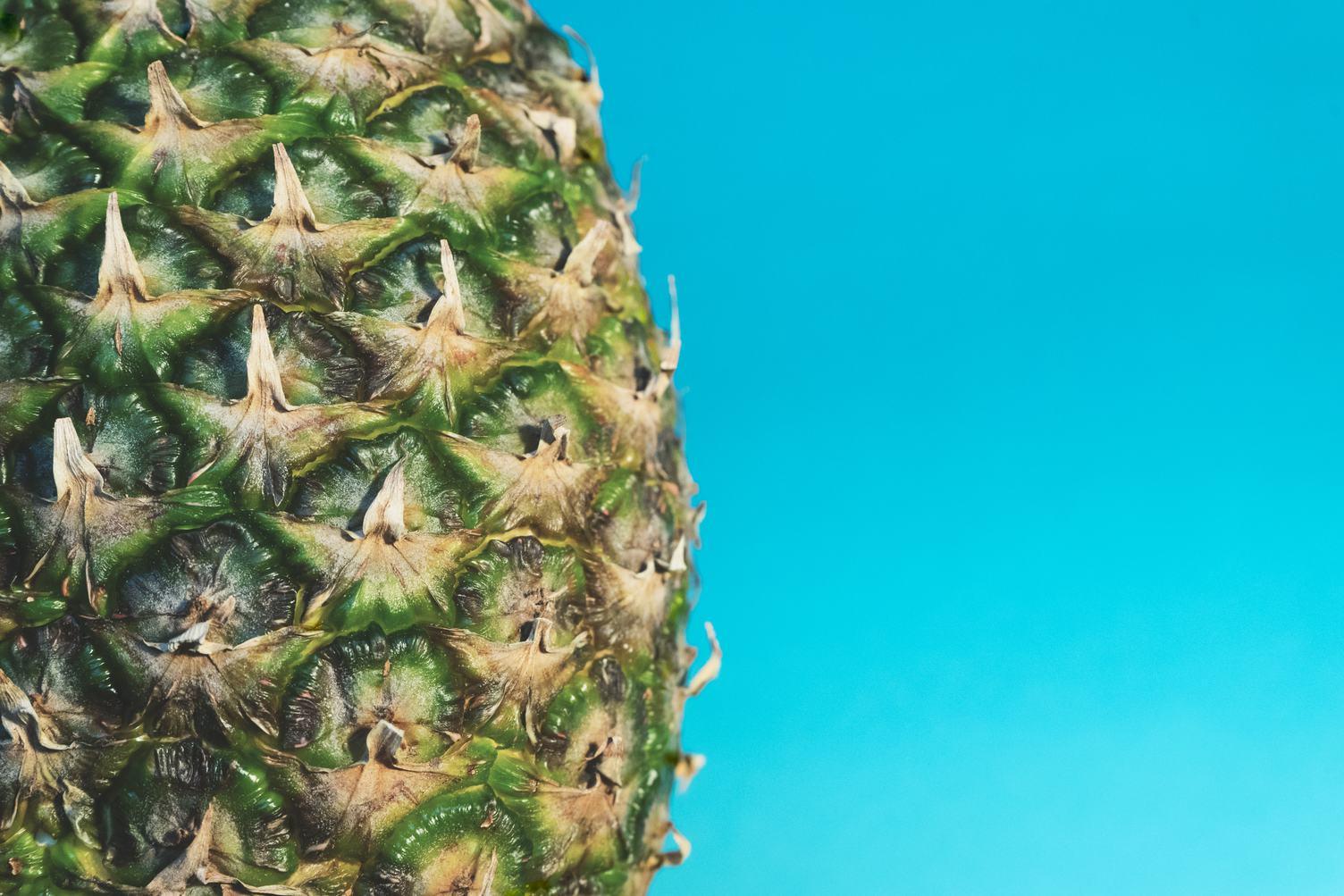Pineapple Skin Closeup against Blue Wall