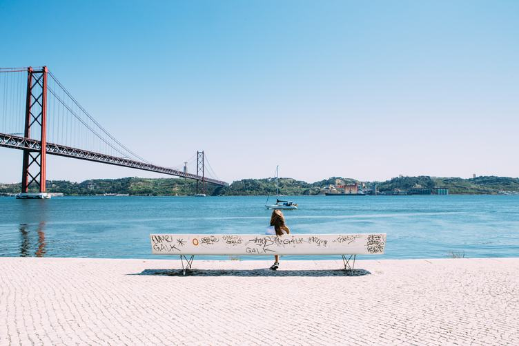 Young Girl sitting on the Bench near the 25th of April Bridge, Lisbon