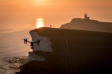 The Person Controls the Dron on the Cliff during the Sunset
