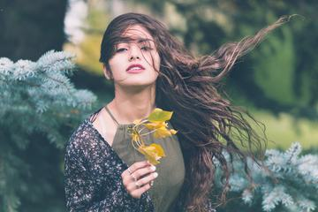 Attractive Girl with Long Blowing Hair in the Garden