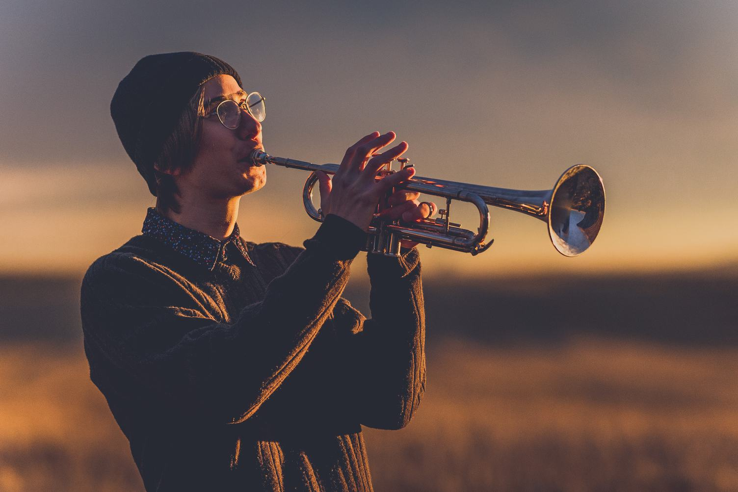 Young Man with Black Hat Playing a Trumpet at Sunset