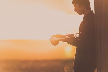 Young Man with Trumpet at Sunset