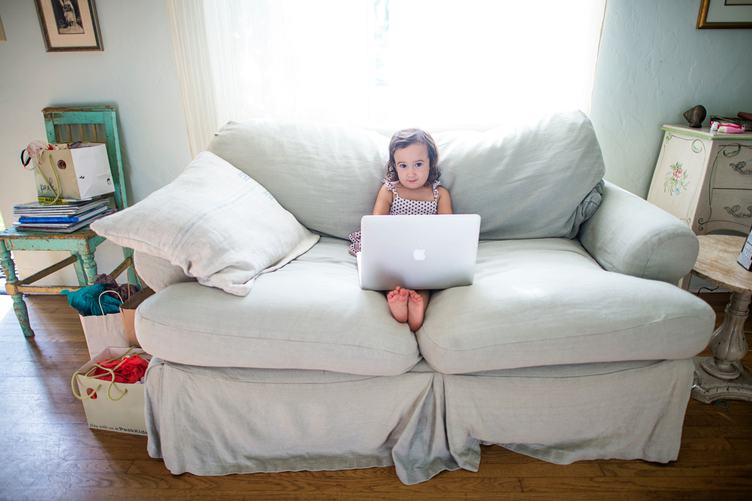 Little Girl Sitting on a Couch with MacBook on Her Lap