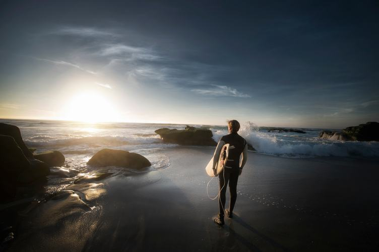 Surfer Walking on the Beach at Sunset
