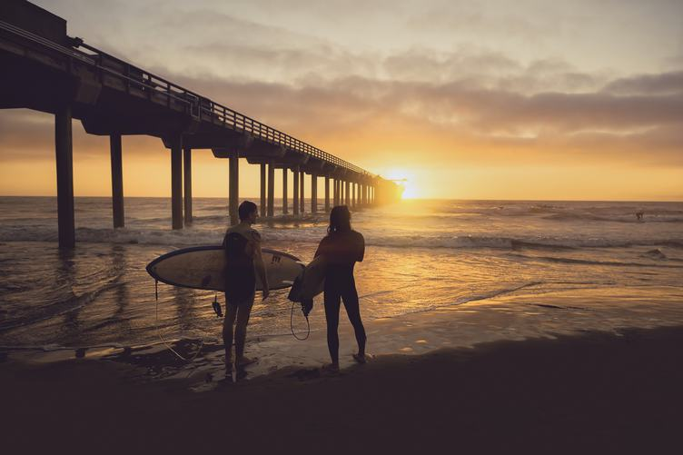 Silhouette of Two Surfers Carrying Their Surfboards on Sunset