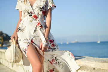 Woman Wearing Floral Dress Walking on the Sea Shore