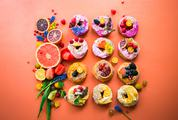 Spring Composition of Delicious Donuts Fruits and Colourful Flowers