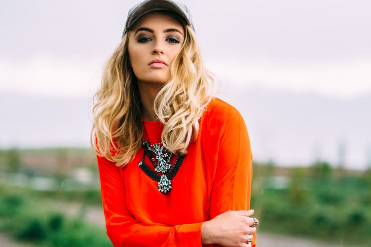 Blonde Wearing Orange Blouse, Necklace and Hat