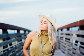 Young Blonde Girl with Cowboy Hat on the Bridge