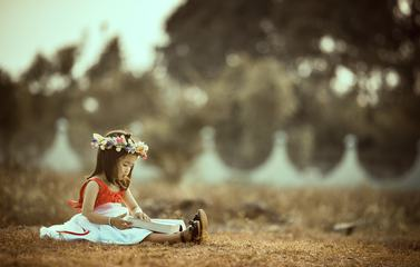 Asian Little Girl Sitting with a Book