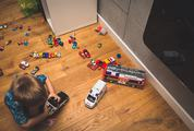 Little Boy Playing with Lots of Colorful Car Toys Indoor