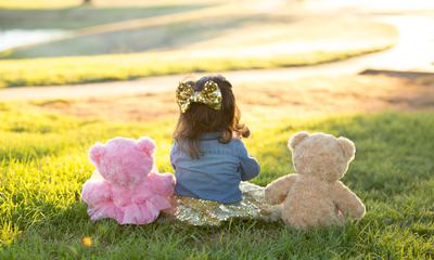 Little Girl Sitting on the Grass with Her Teddy Bears