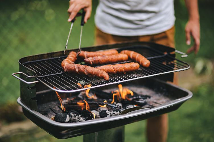 Man Grilling Sausages Outdoors
