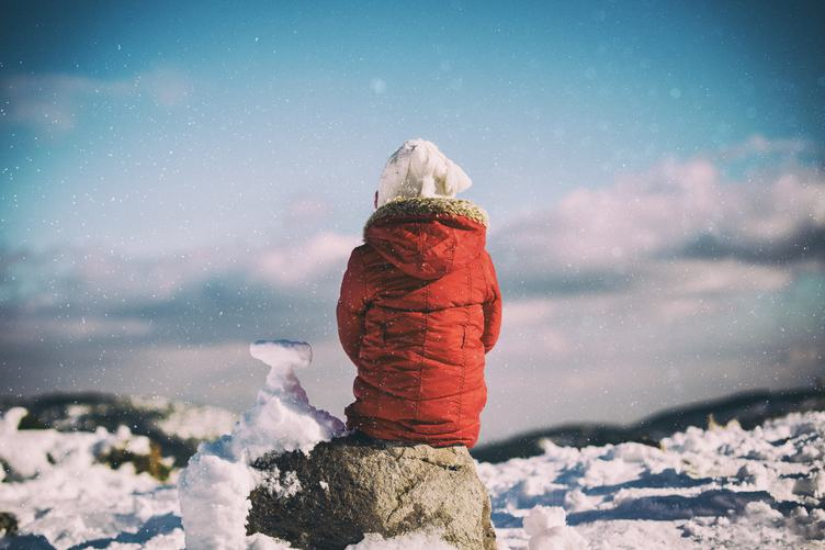 Child Sitting on the Rock when It Is Snowing