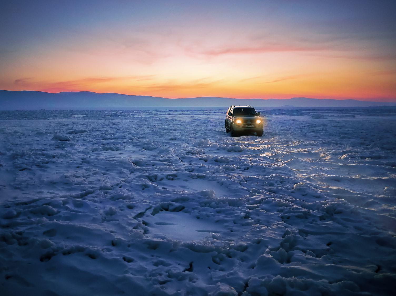 Car on an Frozen Lake Baikal at Sunset