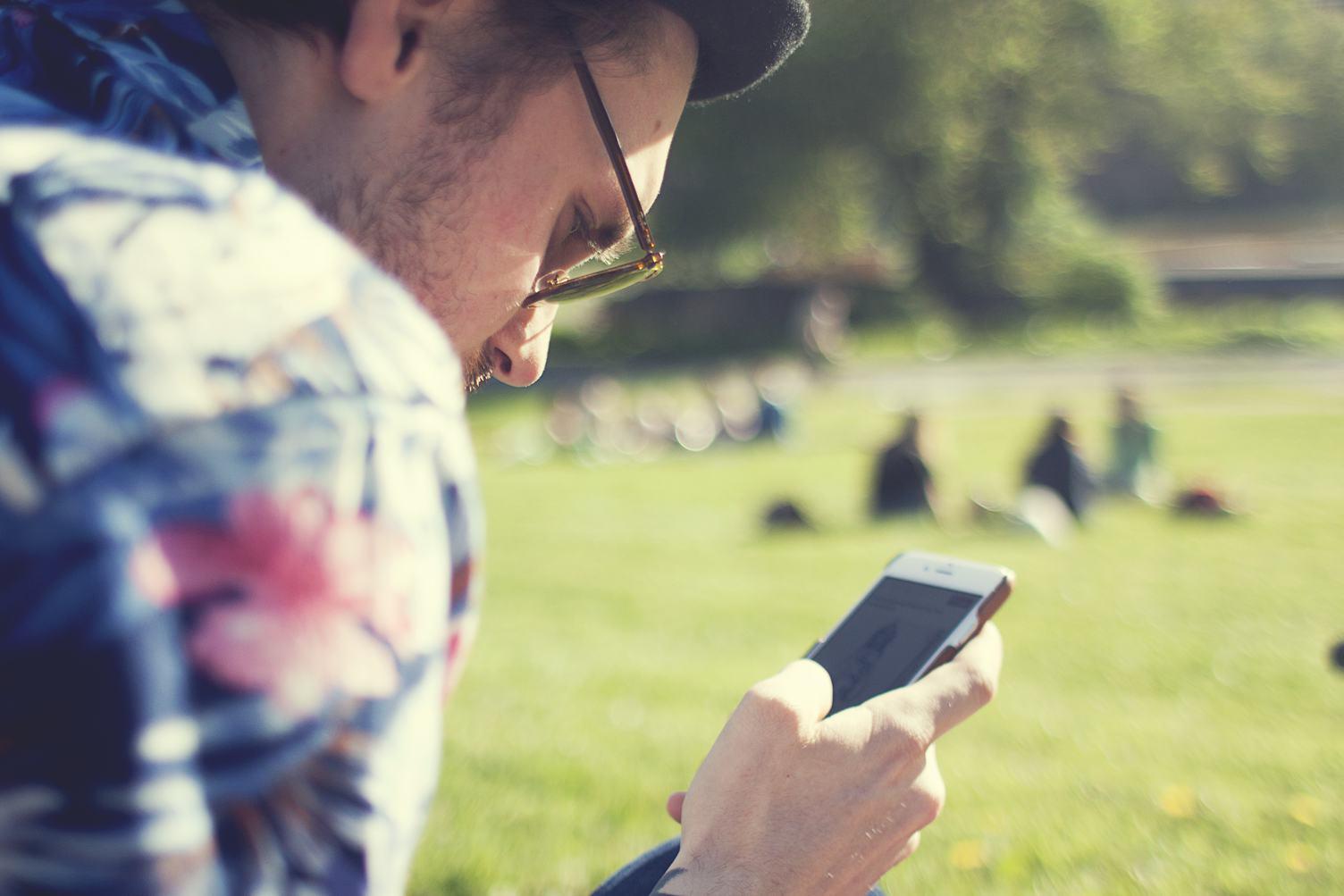 Man  Holding Smartphone on Blurred Background