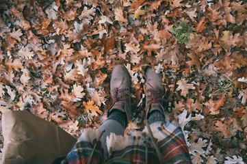Legs in Leather Boots Standing on a Ground with Autumn Leaves