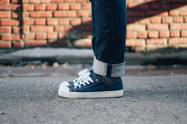 Standing in Sneakers and Jeans on the Street
