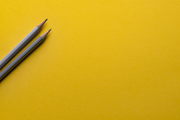 Two Pencils on Yellow Paper