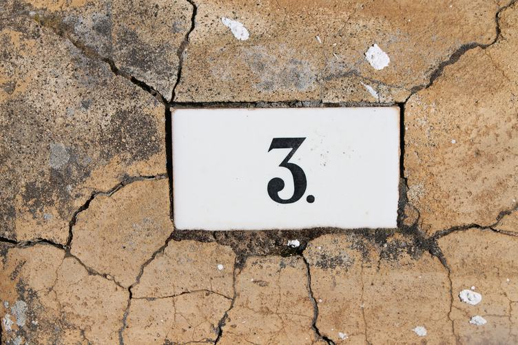 Number Three Sign on Old Cracked Wall