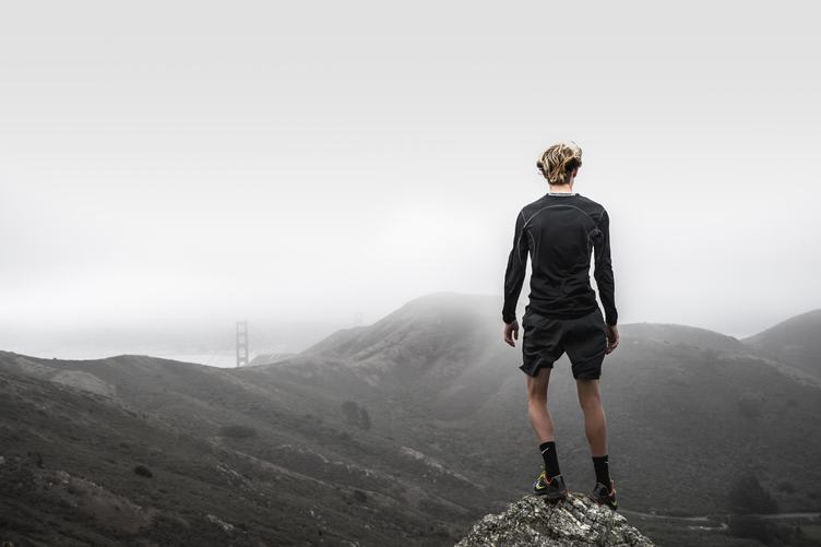 Runner Standing on Top of a Hill and Enjoying View