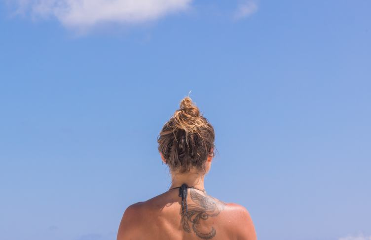 Tanned Woman's Back against the Blue Sky