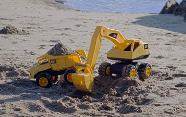 Excavator and Tipper Toys on the Beach Working with Sand