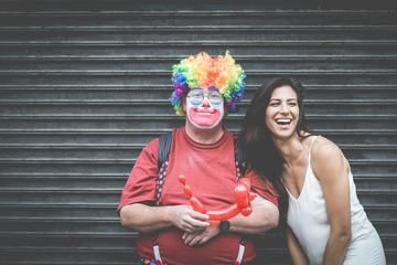Man Dressed up as a Clown with a Laughing Woman