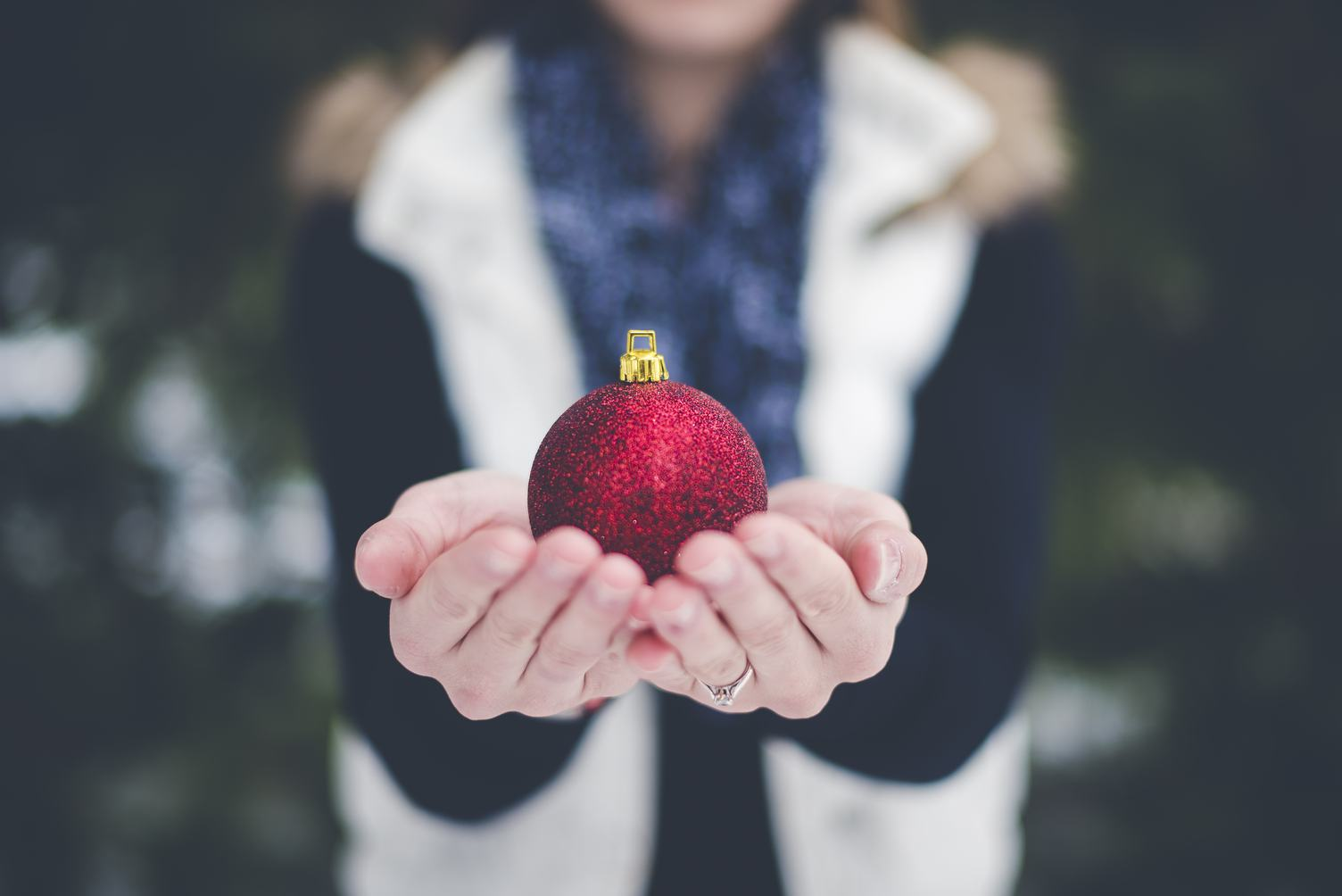 Female Hands Holding Christmas Ball Outdoors