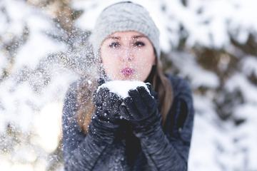 Young Woman Blowing Snow toward Camera Outdoors
