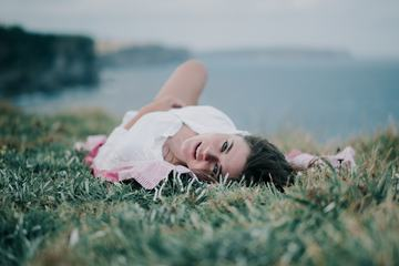 Joyful Young Woman Lies on the Grass