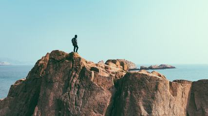 Young Man with Backpack Is Standing on Cliff's Edge and Looking