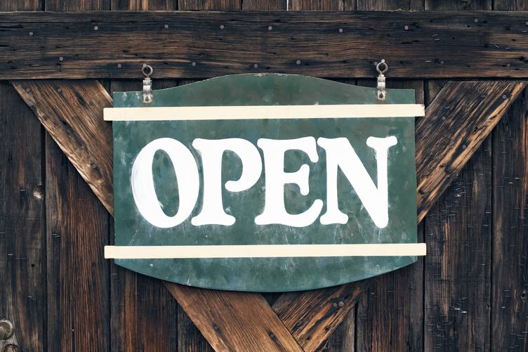 Vintage Open Signboard on Old Wooden Door