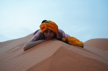 Woman in a Turban Is Lying on the Sand Dune