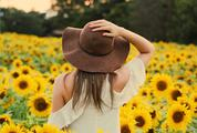 Woman Standing Back in Sunflowers Field