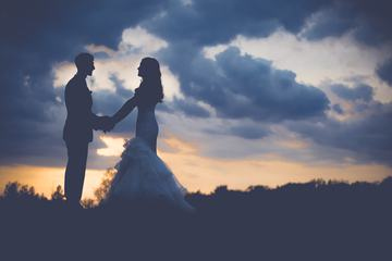 Wedding Couple on the Hill Holding Hands at Sunset