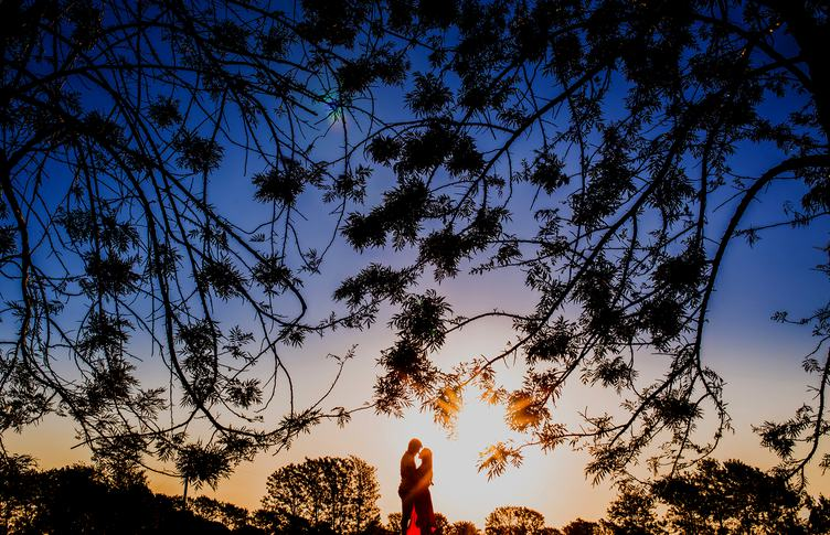 Young Couple Enjoying the Sunset in the Meadow