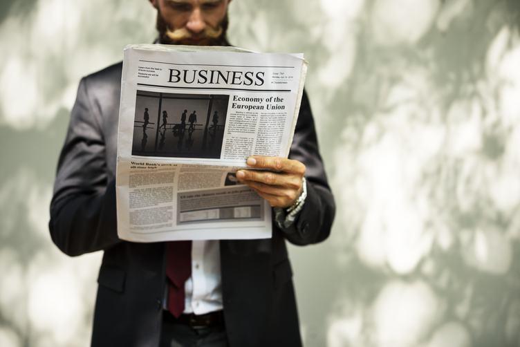 Businessman Holding a News Outdoors