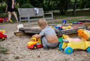 Boy in a Sandbox Playing with a Truck